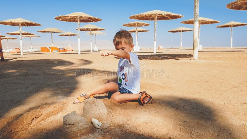 Portrait of cute little boy making sand castle on the sea beach royalty free stock images
