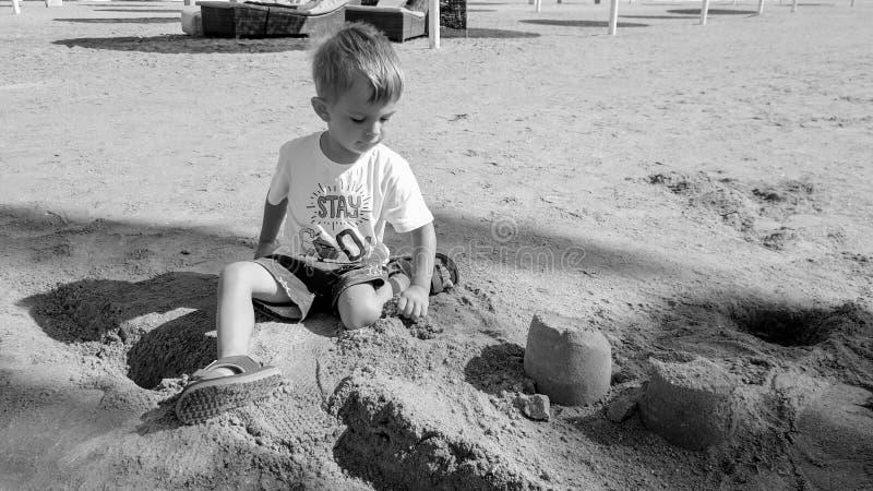 Portrait of cute little boy making sand castle on the sea beach stock photos