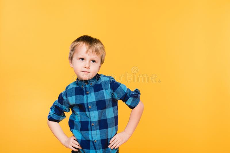 Portrait of little boy in shirt standing akimbo. Isolated on yellow stock photography