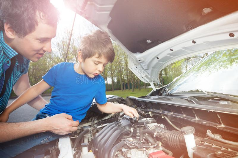 Little boy watching his father work on car engine royalty free stock photos