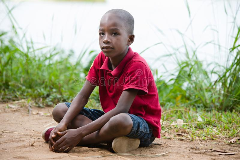 Portrait of little boy sitting alone in the heart of nature. Portrait of little boy sitting cross-legged alone in nature at the edge of a lake stock images