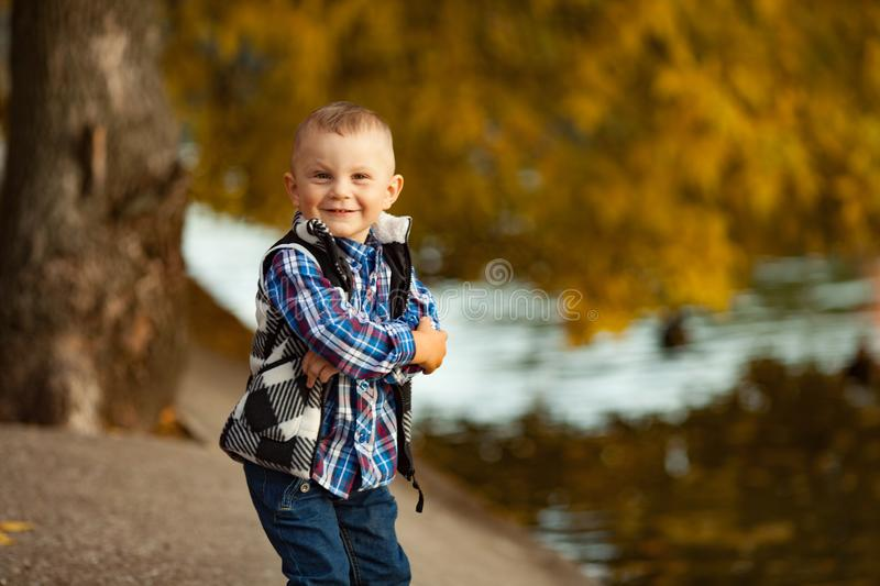 Portrait of a little boy during a walk in the park in autumn. stock photo
