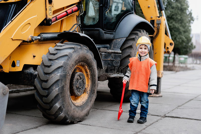 Portrait of little builder in hardhats working outdoors near Tractor excavator. royalty free stock images