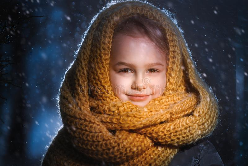 Portrait of a little charming girl in a yellow wool scarf standing outside during a snow blizzard royalty free stock photos