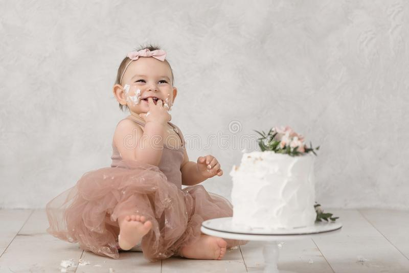 Portrait of a little cheerful birthday girl with the first cake. Eating the first cake. Smash cake stock image
