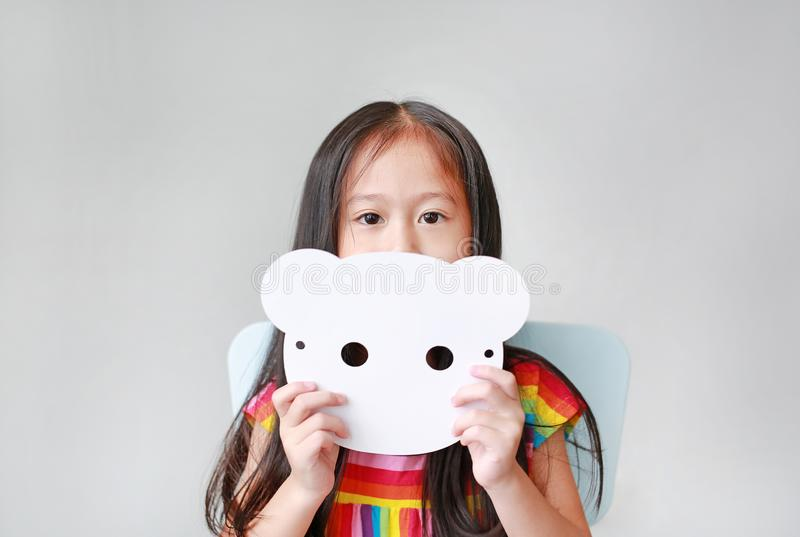 Portrait of little child girl holding blank white animal paper mask fronting her face on white background. Idea and concept for. Kid dressed up planimal face royalty free stock image