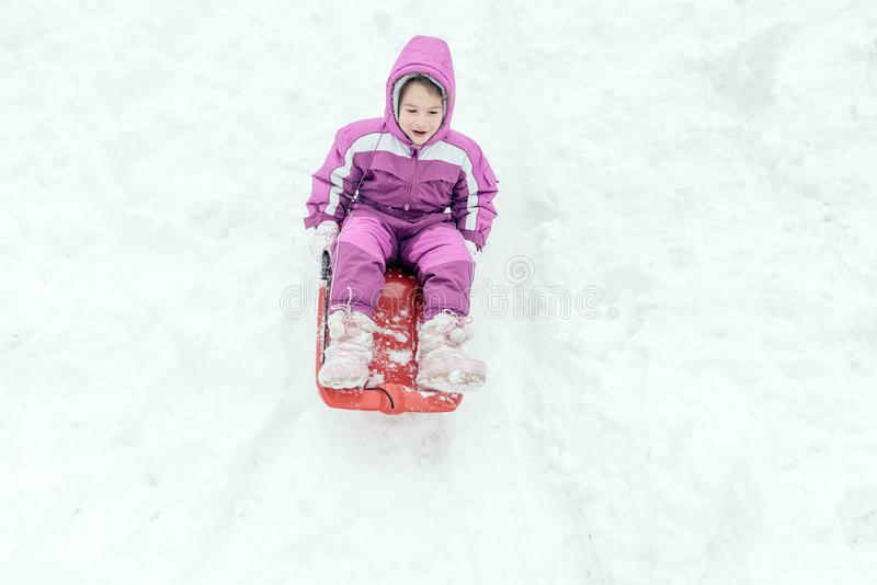 Portrait of the little child outdoor. Happy little girl sliding in the snow royalty free stock photo