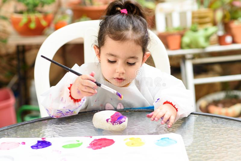 Cute little girl having fun, coloring with brush, playing and painting. Preschooler with paint at garden. stock photo