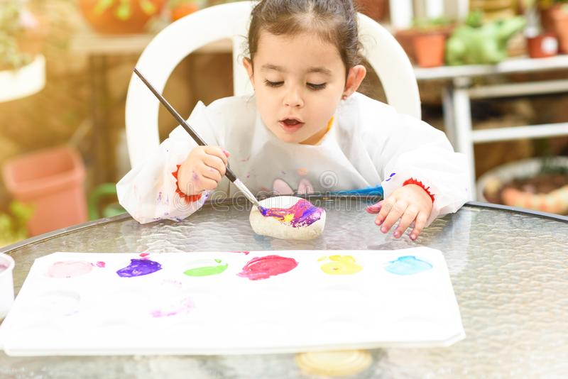 Cute little girl having fun, coloring with brush, playing and painting. Preschooler with paint at garden. royalty free stock images