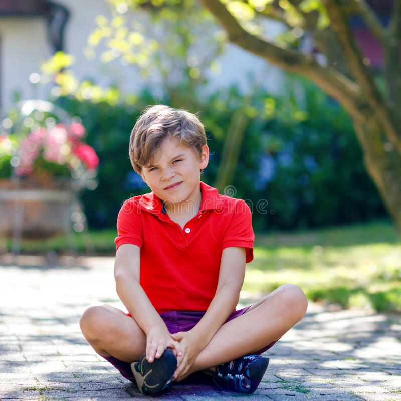 Portrait of little cool kid boy sitting on ground on sunny day in domestic backyard. Happy healthy child having fun on royalty free stock photography