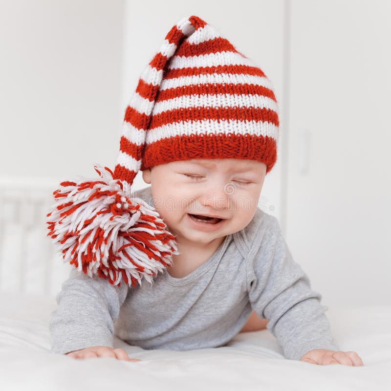 Portrait of little crying infant child. In funny knitted hat lying on bed royalty free stock photos