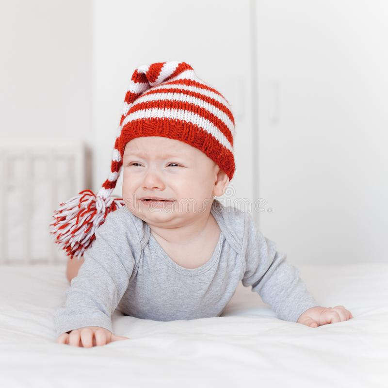 Portrait of little crying infant child. In knitted hat lying on bed stock photo
