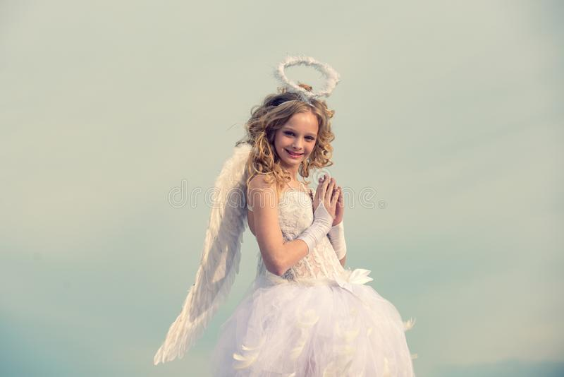 Portrait of little curly blond Angel girl. Beauty blue her eyes - charming lady in the heaven sunlight. Girl dressed as. An angel on a light heaven background stock images