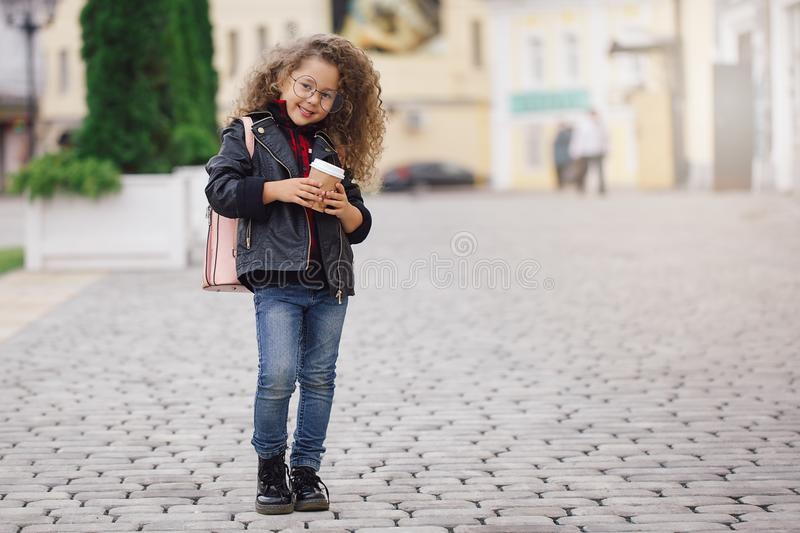 Portrait of little curly hipster girl in glasses with coffee. Urban style. Autumn royalty free stock photos