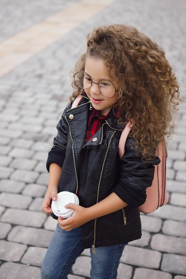 Portrait of little curly hipster girl in glasses with coffee. Urban style. Autumn royalty free stock photography