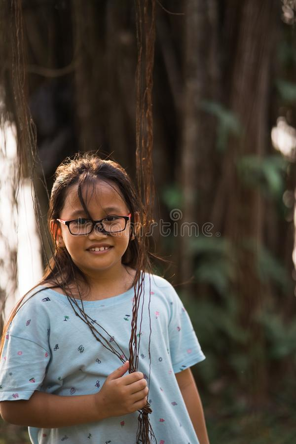 Portrait of Little cute child girl standing alone with near banyan tree stock image