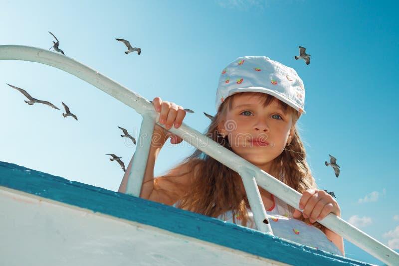 Portrait of little cute girl enjoying playing on boat stock photo
