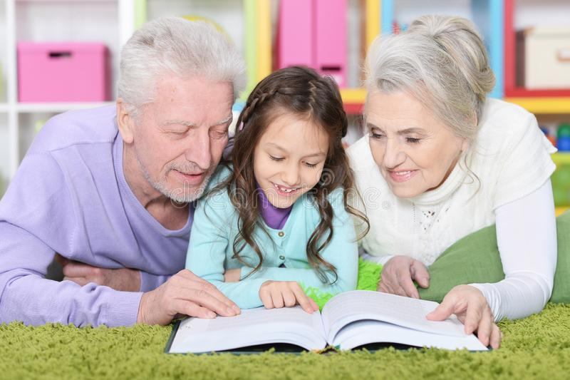 Portrait of little cute girl with grandparents studying royalty free stock photography
