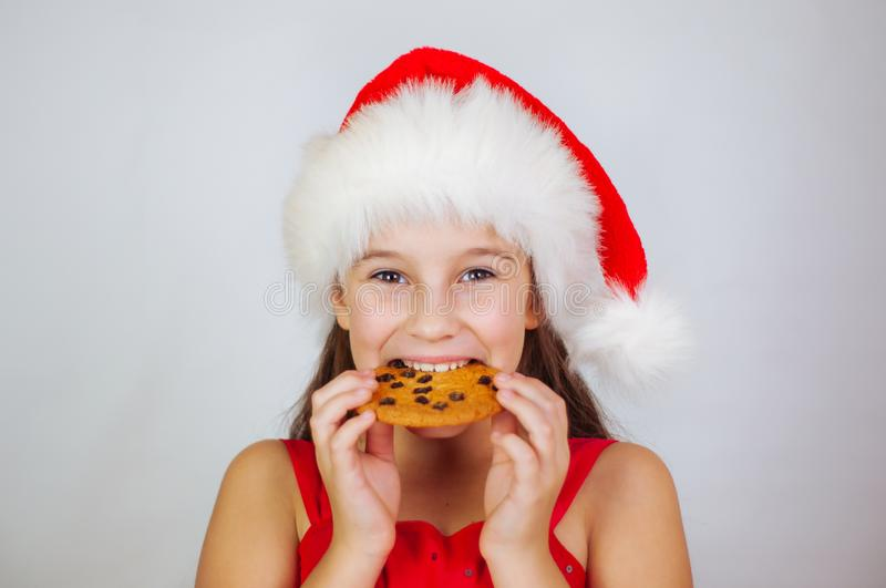 portrait little cute girl in santa hat eating christmas cookies stock photography