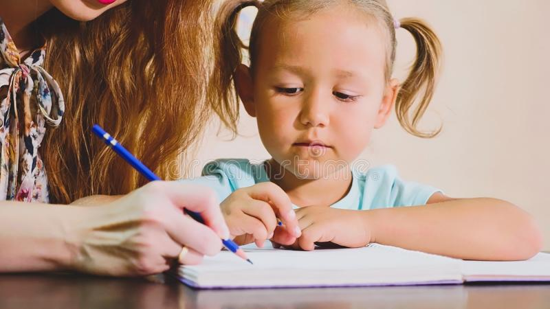 Little cute girl sits in classroom and studies with teacher in exercise book stock images