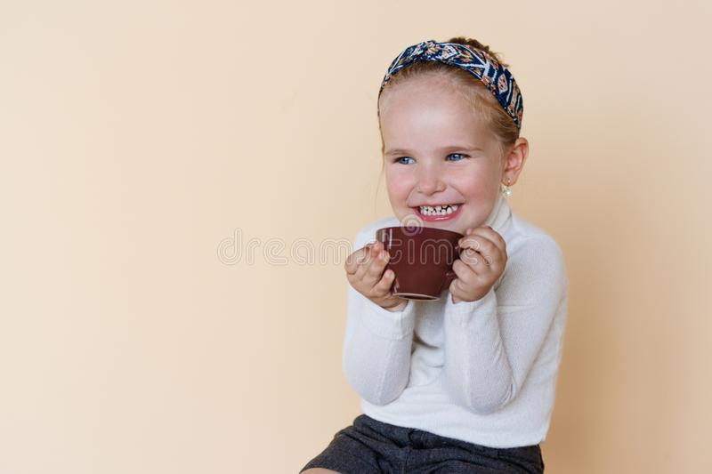 Portrait of a little cute girl sitting and smiling, holding cup of hot drink cocoa enjoying, over beige background. stock photography