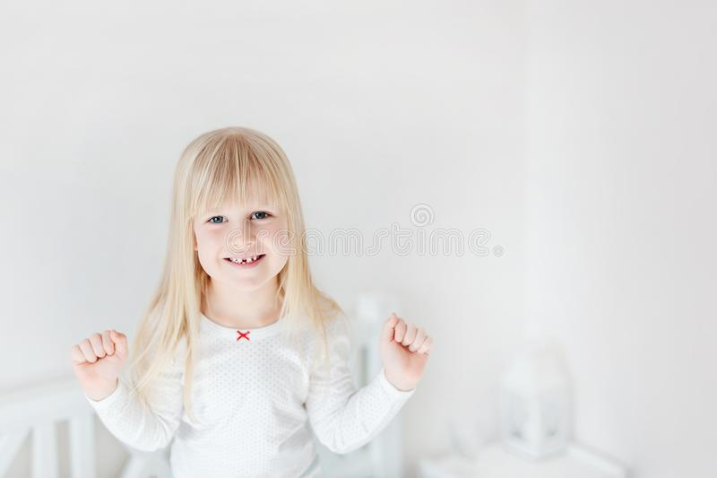 Portrait of little cute girl standing on bed. Adorable smiling child. Blond kid raising up fists. Children victory o royalty free stock photos
