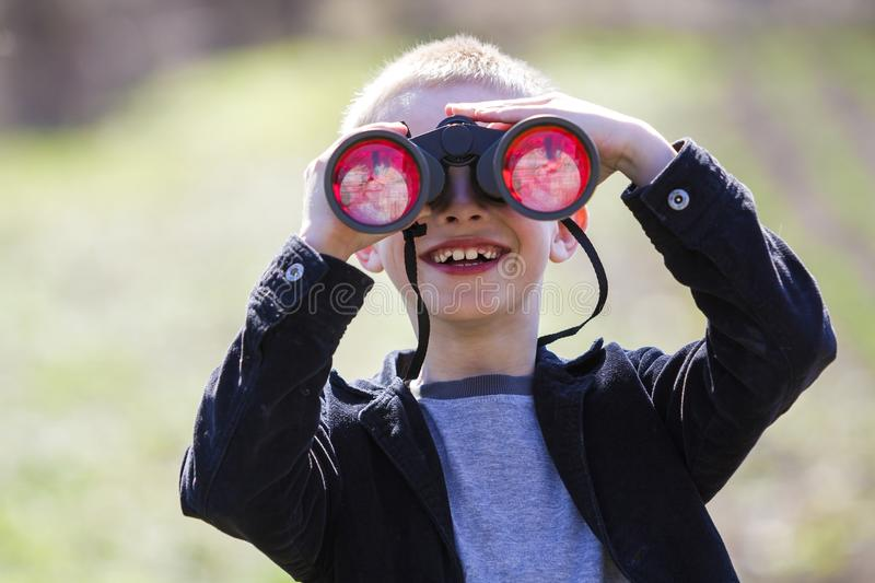Portrait of little cute handsome cute blond boy watching intently something through binoculars in distance on blurred background. royalty free stock images