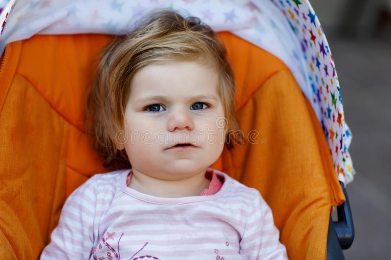 Portrait of little cute toddler girl sitting in stroller or pram and going for a walk. Happy cute baby child having fun stock photos