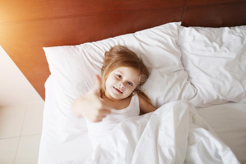 Portrait of little daughter show thumbs up like smile laying at white bed home on sunny good morning. Cute portrait of kid daughter show thumbs up like smiling royalty free stock photography