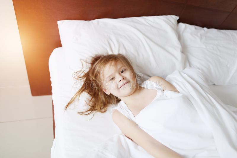 Portrait of little daughter silly play and smile at bed home on sunny good morning. Portrait of cute little daughter smiling at bed home on sunny good morning stock photos