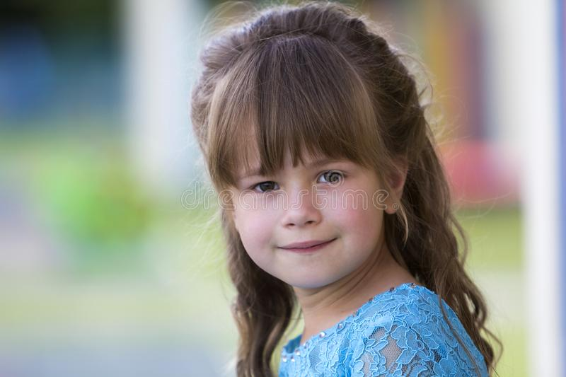 Portrait of little fashionable blond girl in blue dress, with gray eyes and beautiful long hair smiling in camera on bright blurre royalty free stock images