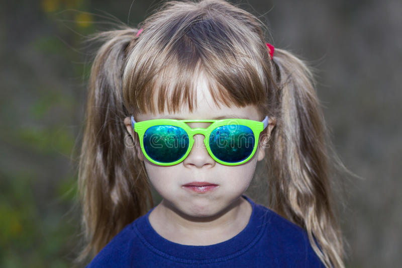 Portrait of little fashionable girl in green sunglasses outdoors royalty free stock photo