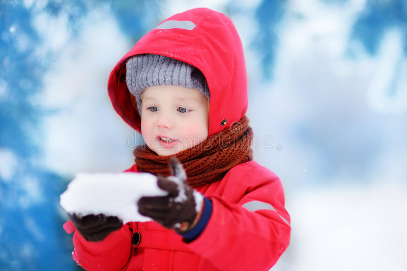 Portrait of little funny boy in red winter clothes having fun with piece of ice. Active outdoors leisure with children in winter. Kid with warm hat, hand royalty free stock photography