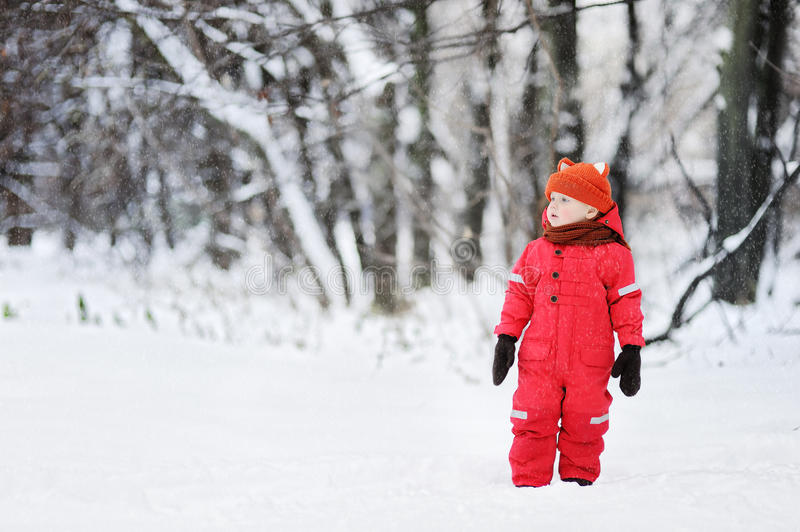 Portrait of little funny boy in red winter clothes having fun with snow during snowfall stock photos