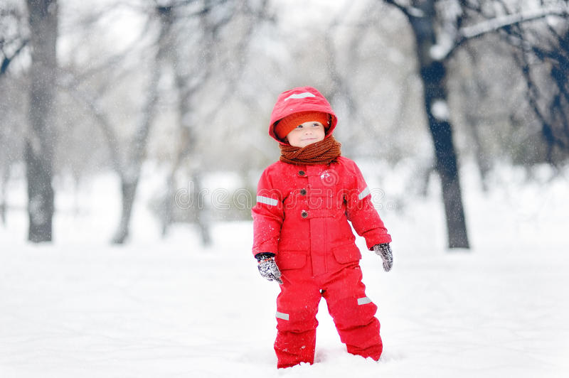 Portrait of little funny boy in red winter clothes having fun with snow during snowfall royalty free stock photo