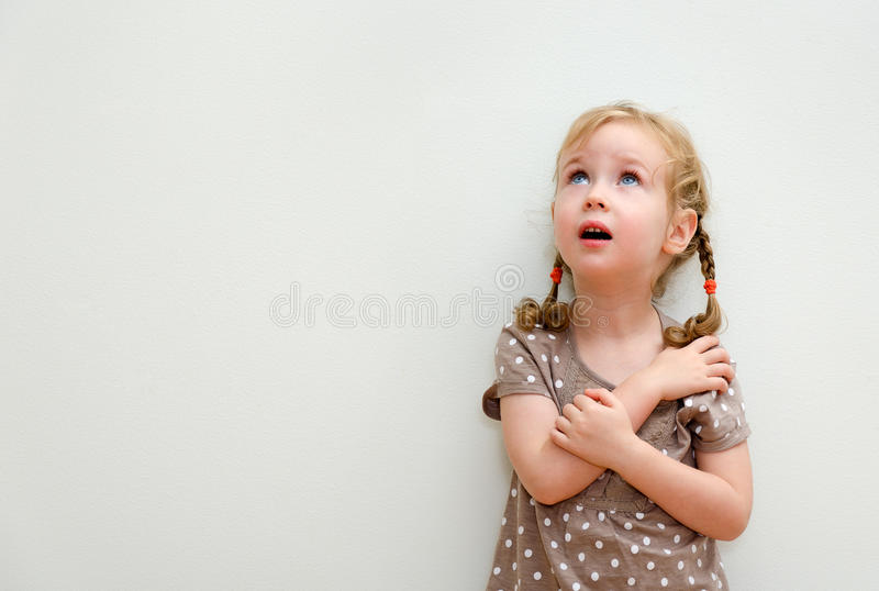 Portrait of little girl. Standing against the wall and looking up stock image