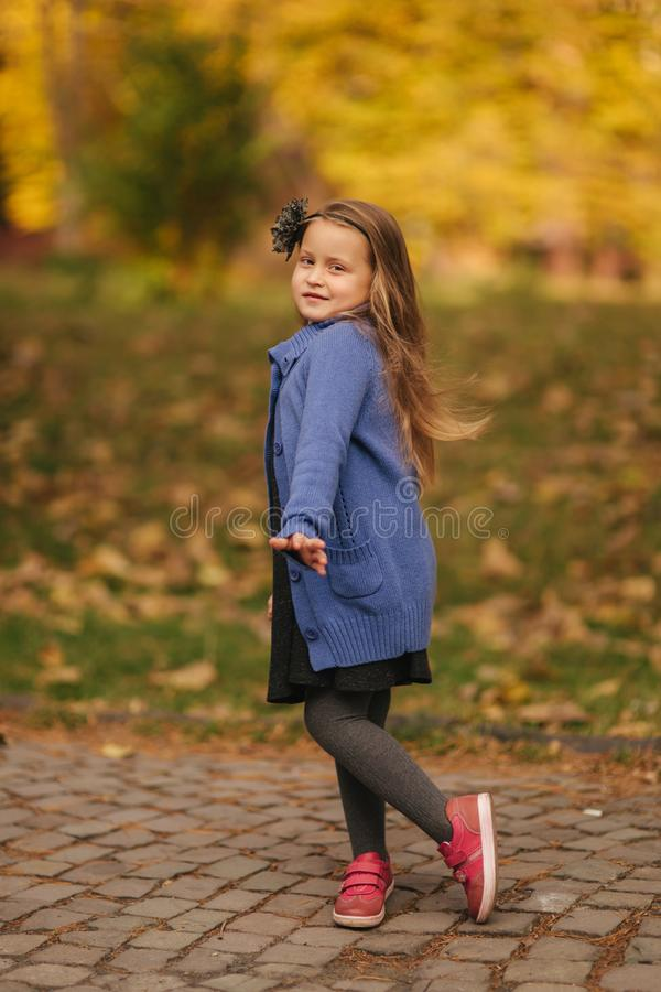 Portrait of little girl in the autumn park. Girl model poses to photographer. Happy child royalty free stock image
