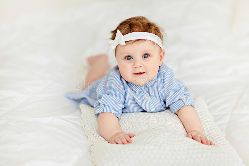 Portrait of a little girl baby with blue eyes in a striped blue. Blouse lying on the bed with Lacy pillow royalty free stock images