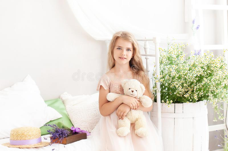 Portrait of a little girl on the bed in a bright bedroom in the morning. Blonde cute girl with long hair hugs a teddy bear in her stock photo