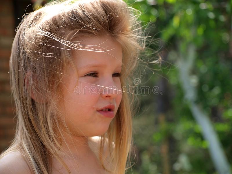 Portrait of a little girl with blond hair disheveled by the wind. On a background of green nature on a summer day in the garden stock image