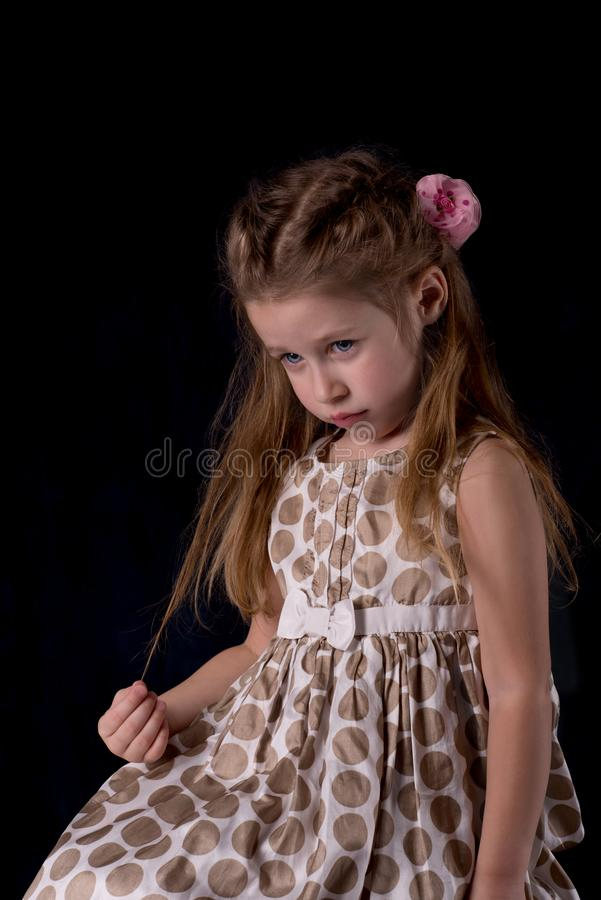 Portrait of the girl of the blonde with blue eyes. Portrait of the little girl of the blonde with blue eyes on dark background royalty free stock images