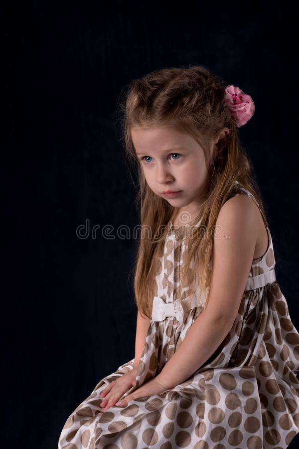 Portrait of the girl of the blonde with blue eyes. Portrait of the little girl of the blonde with blue eyes on dark background stock photos