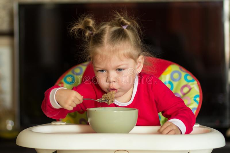 Portrait of little girl blowing on hot porridge to cool sitting in feeding chair stock photography
