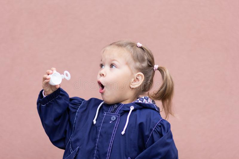 Portrait of the little girl blowing soap bubbles on the pink background royalty free stock photography