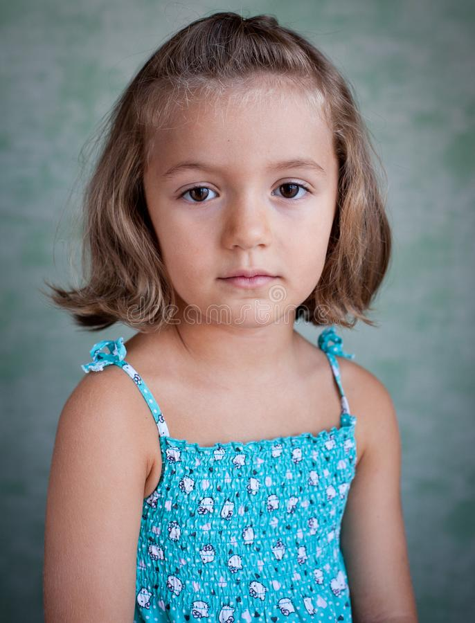 Portrait of a little girl on a blue background royalty free stock photography