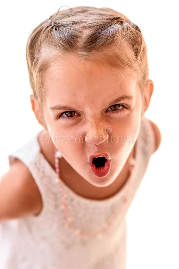 Portrait of a little girl with braids screaming. Child with braided hair is looking at the camera, yelling stock photography