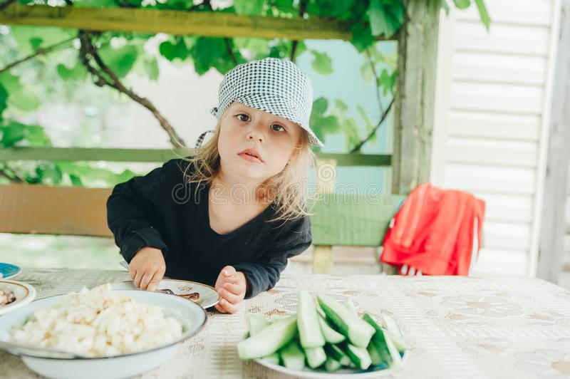 Portrait of the little girl in a cap behind a dining table at the dacha. Family holiday in the country royalty free stock photography