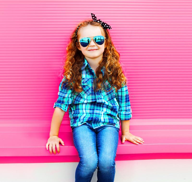 Portrait little girl child in checkered shirt, sunglasses on colorful pink wall royalty free stock photo