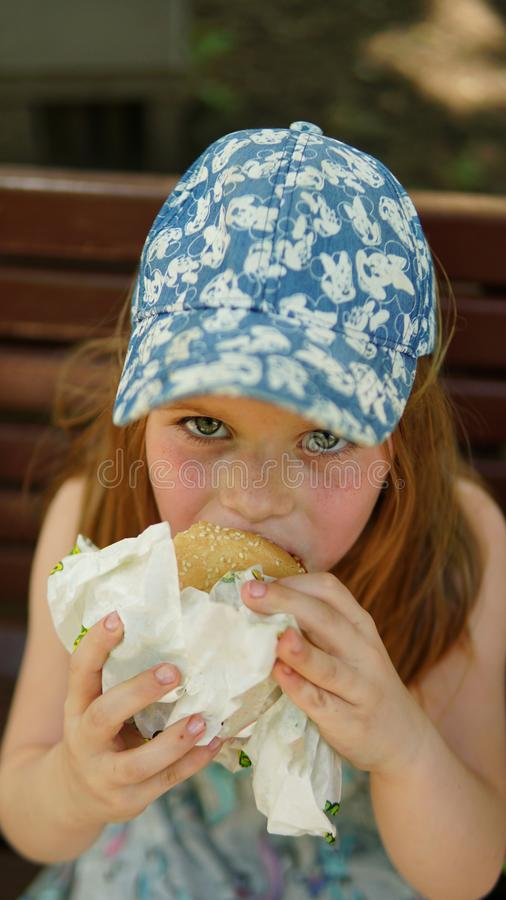 Portrait of a little girl . A child eating hamburger in the Park stock image