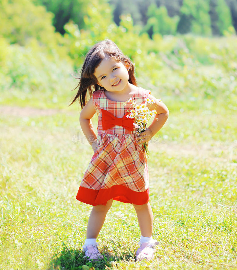 Portrait of little girl child with flowers wearing a dress. Outdoors in summer day stock photos